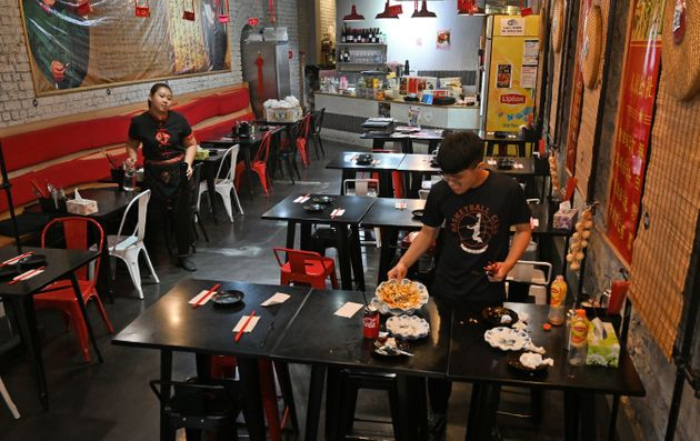 This photo taken on February 14, 2020 shows staff clearing a table at a Chinese restaurant in Melbourne's