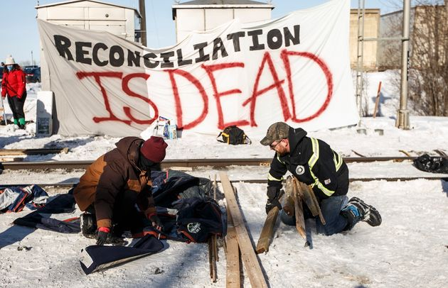 A supporter of the Wet'suwet'en hereditary chiefs, left, and a counter protestor remove a blockade after...