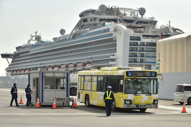 A bus carrying passengers who disembarked from the Diamond Princess cruise ship (back), in quarantine...