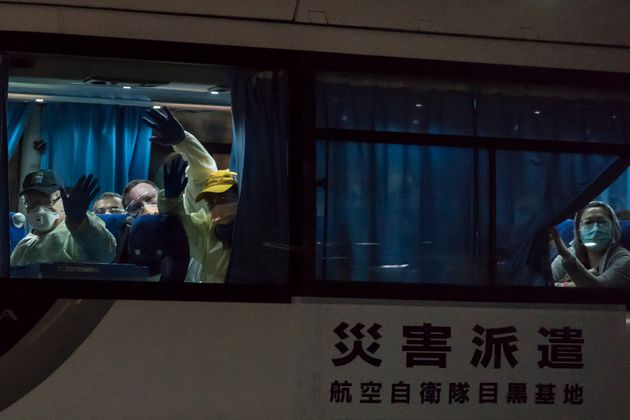 People wave from a bus carrying passengers, who boarded the Qantas aircraft chartered by the Australian government, from the quarantined Diamond Princess cruise ship drive at the Daikoku Pier on February 19, 2020 in Yokohama, Japan.