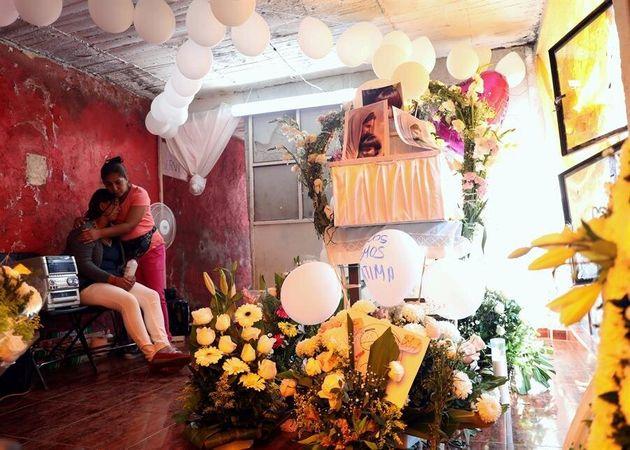 María Magdalena Anton (i) recibe el consuelo de una mujer durante el funeral de su hija Fátima este