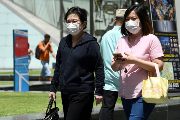 Two women wearing protective facemasks, amid concerns over the spread of the COVID-19 coronavirus, walk...