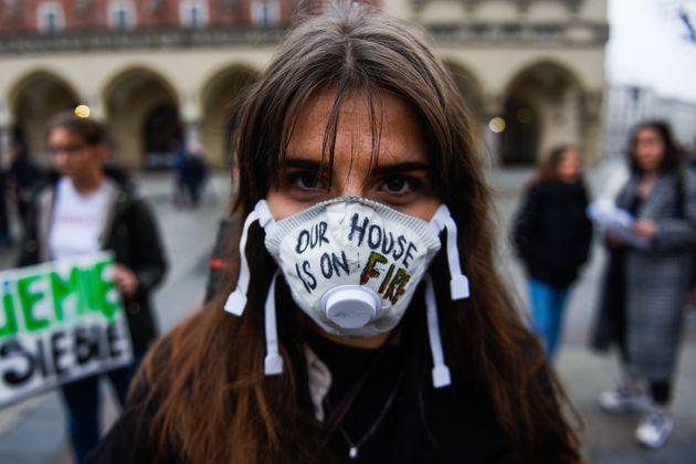 Une jeune fille proteste en portant un masque sur lequel est écrit