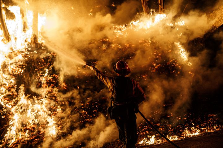 A firefighter sprays water while battling the spread of the Maria Fire as it moved quickly towards Santa Paula, California, on Nov. 1, 2019.