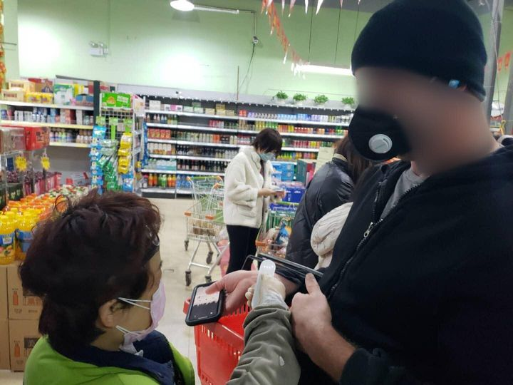 One of the authors getting his temperature checked as he enters the grocery store.