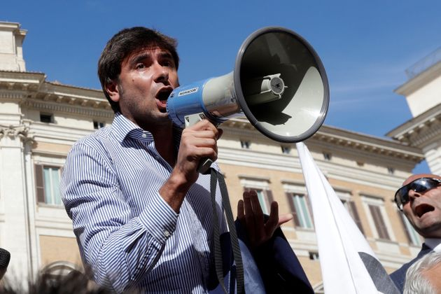 Five Star Movement Lawmaker Alessandro Di Battista uses a megaphone to talks with demonstrators of the...
