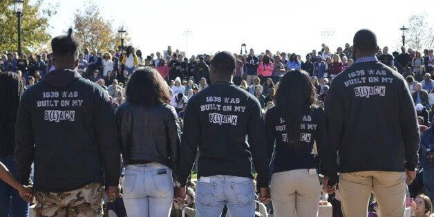 Members of Concerned Student 1950 join hands at a press conference at Traditions Plaza at Carnahan Quad, on the University of