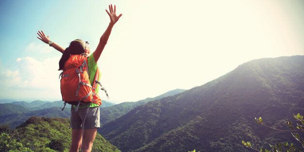 cheering woman hiker open arms at mountain peak cliff