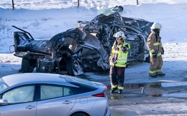 Firemen stand next to a demolished car following a massive pileup involving numerous vehicles on the...