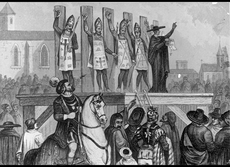 Circa 1400, Heretics are tortured and nailed to wooden posts during the Inquisition.