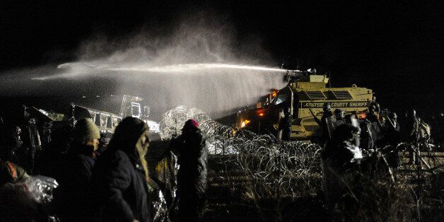 Police use a water cannon on protesters during a protest against plans to pass the Dakota Access pipeline near the Standing R