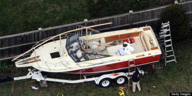 WATERTOWN, MA - APRIL 20: Investigators work around the boat where Dzhokhar A. Tsarnaev was found hiding after a massive manh