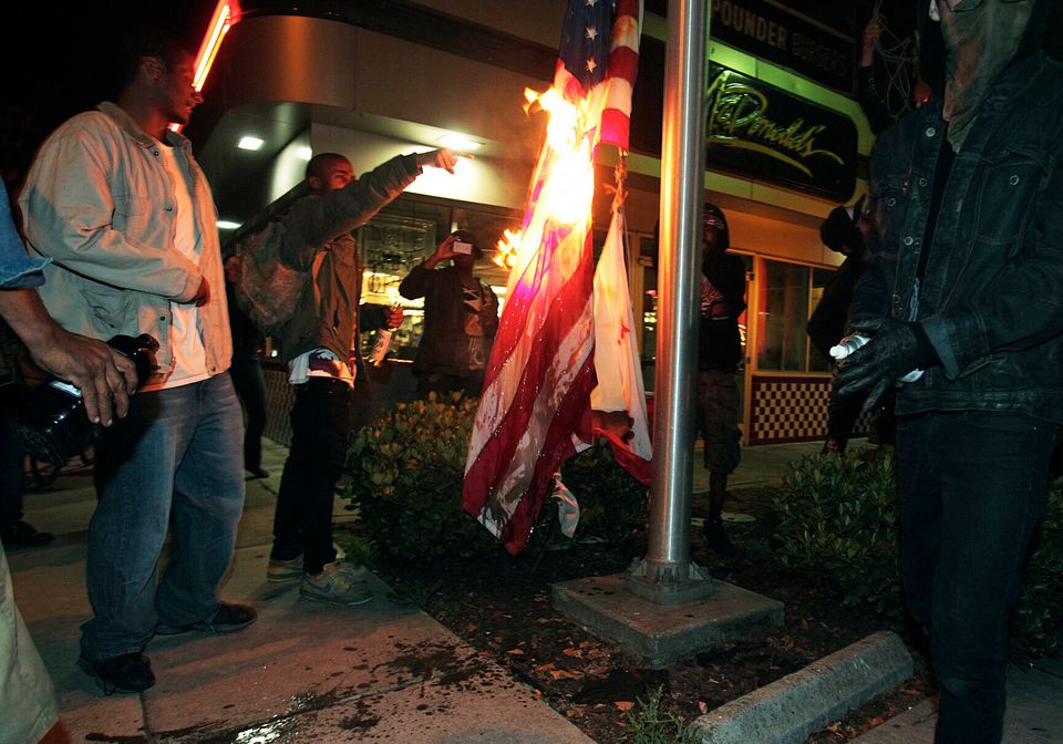 Marchers burn a United States flag outside a fast food restaurant during a protest after George Zimmerman was found not guilt