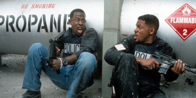 Martin Lawrence and Will Smith yelling at each other while holding machine guns to defend themselves in a scene from the film