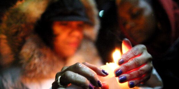 STATEN ISLAND, NY - DECEMBER 05: (L-R) Michele Sledge and Shannon Watkins light candles near Eric Garner's memorial for a can