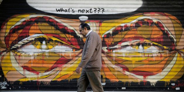 In this photo made on Tuesday, April 29, 2015, a Greek man walks past a graffiti in central Athens. Wednesday May 6 marks fiv