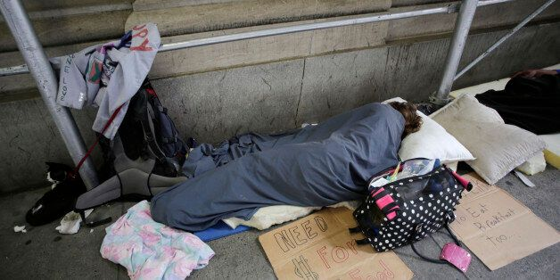 Homeless people sleep on the sidewalk in New York's financial district, Monday, Aug. 19, 2013 in New York. (AP Photo/Mark Len