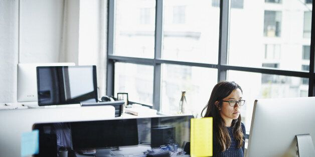 Businesswoman sitting at desk in high tech startup office working on computer