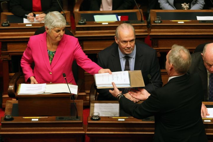 Premier John Horgan looks on as Minister of Finance Carole James passes on a copy of the budget.