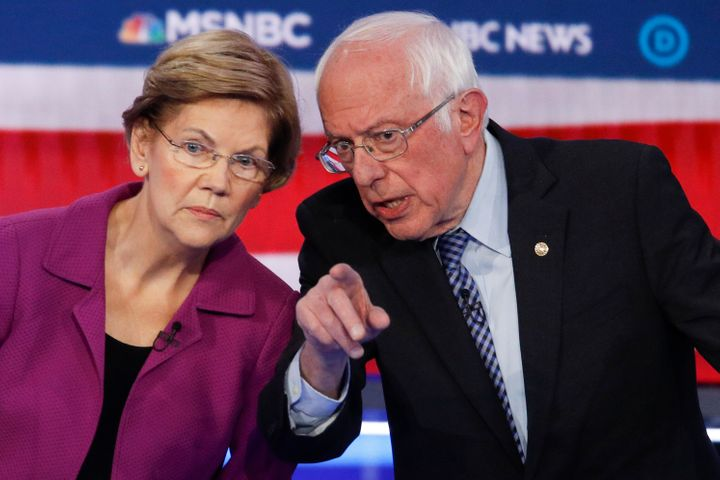 Sen. Elizabeth Warren and Sen. Bernie Sanders talk during a Democratic presidential primary debate on Feb. 19, 2020.