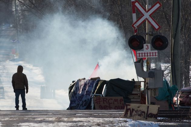 A protester stands beside smoke at the closed train tracks in Tyendinaga Mohawk Territory near Belleville,...