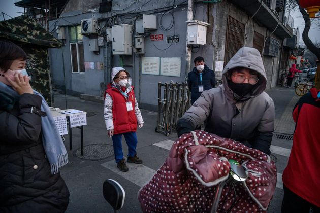 Members of a local neighbourhood committee wear protective masks as they turn away a visitor while standing...