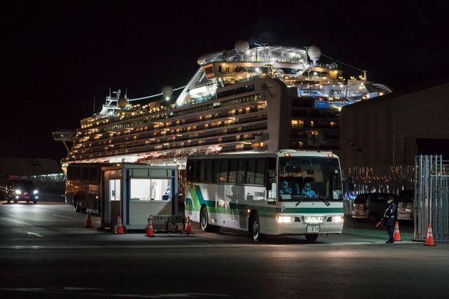 A bus carrying passengers who will take a government charter flight from the quarantined Diamond Princess...