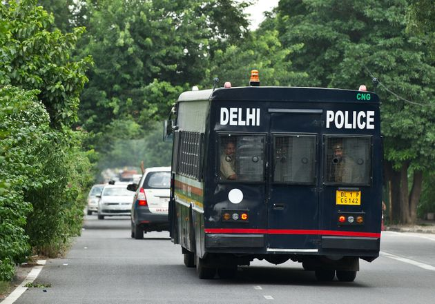A police vehicle believed to be carrying the accused in a gangrape and murder case, leaves the Saket...