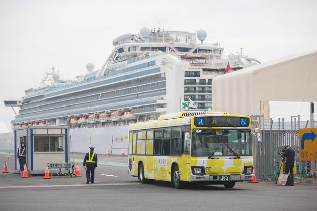 일본 요코하마 항구에 정박한 채 '선상 격리'됐던 크루즈선 다이아몬드 프린세스호에서 내린 승객들을 태운 버스가 항구를 빠져나가고 있다. 2020년