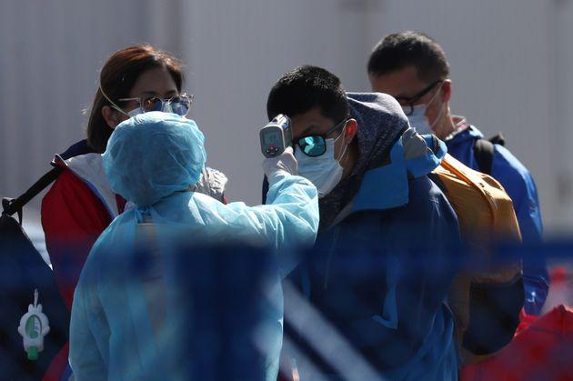 보호복을 입은 일본 보건당국 관계자들이 배에서 내린 승객들을 상대로 체온 측정을 실시하고 있다. 요코하마, 일본. 2020년