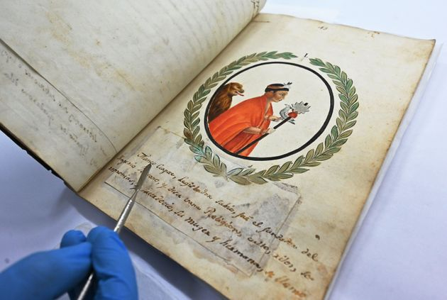 A conservation technician at the Peruvian National Library displays an invaluable manuscript with the...