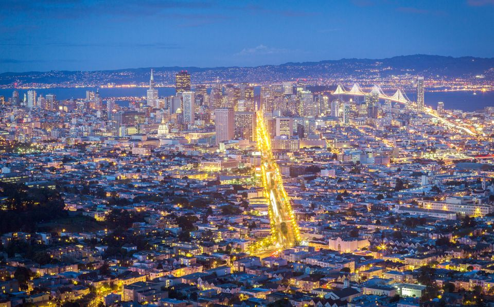 San Francisco at night, with Market Street lit up. Private cars are now banned on the