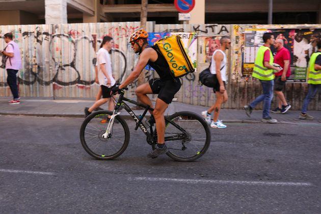 Un repartidor de Glovo, pedaleando por las calles de Madrid, en julio de