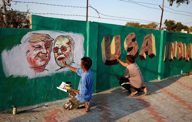 Des hommes s'affairent à compléter une murale le long de la route en prévision du...