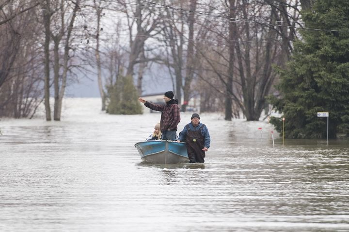 A man pulls people along a flooded residential street in a boat in west Montreal on April 26, 2019. Ottawa's bills for dealing with natural disasters neared half a billion dollars in two of the last three years.