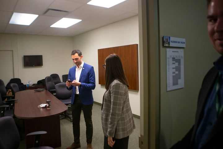 Ontario Education Minister Stephen Lecce is pictured in a Progressive Conservative caucus office as protesters gather outside Queen's Park in Toronto on Feb. 21, 2020.