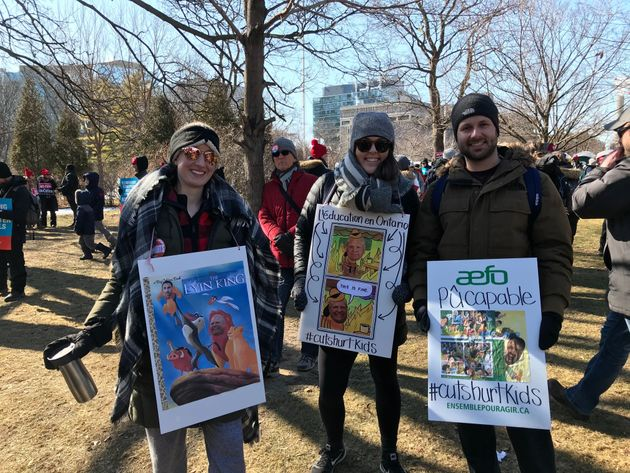 Demonstrators show off their signs about Ontario Premier Doug Ford at a protest organizes by teachers'...