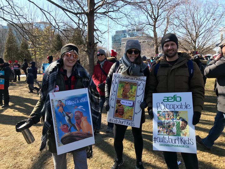 Demonstrators show off their signs about Ontario Premier Doug Ford at a protest organizes by teachers' unions on Feb. 21, 2020.