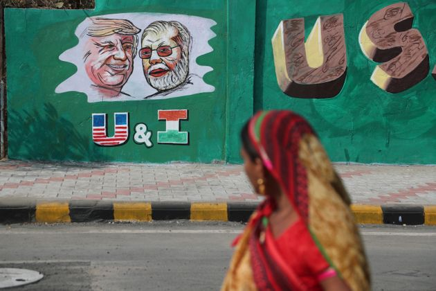 A woman looks at a wall painted with portraits of U.S. President Donald Trump and Prime Minister Narendra...