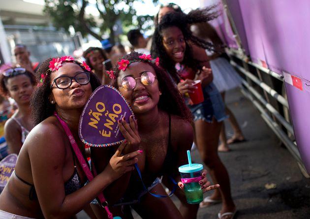 Foliãs posam para foto com placa da campanha