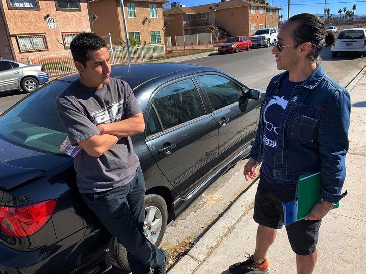 Vaneik Echeverria, right, talks to Adrian Silva, who never votes, about Democratic presidential candidate Bernie Sanders in East Las Vegas.