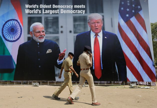 Indian policemen walks past a hoarding welcoming U.S President Donald Trump, at the airport ahead of...