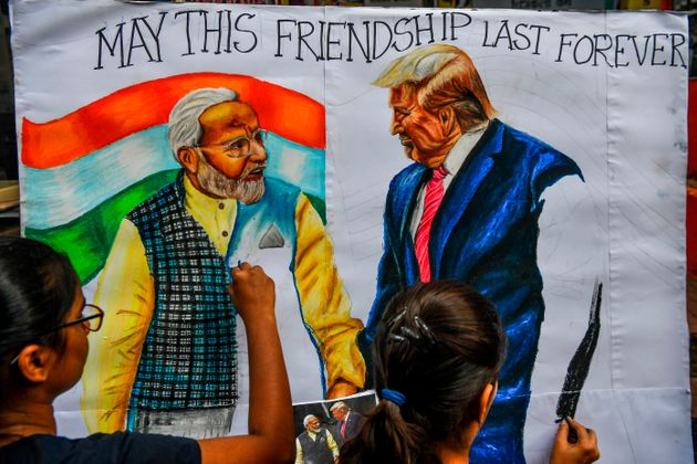 Students paint on canvas faces of US President Donald Trump and India's Prime Minister Narendra Modi...