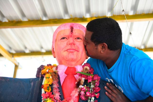 Farmer Bussa Krishna, 33, kisses a statue of US President Donald Trump after offering prayers, at his...