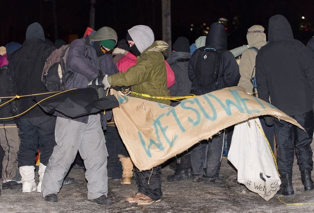 Protesters remove a sign as they leave rail blockade in Saint-Lambert, Que. on