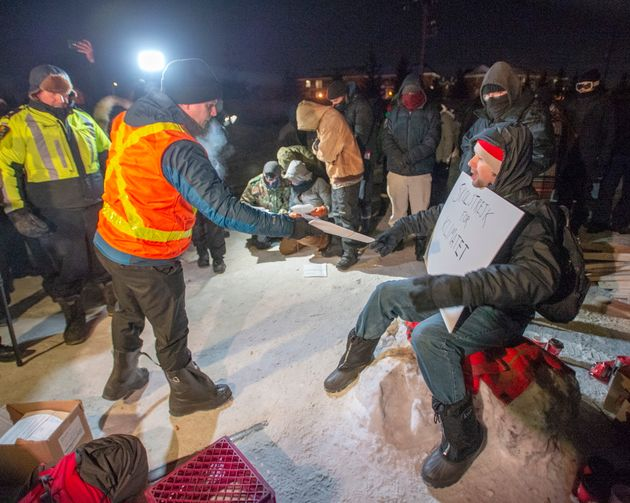 Police serve an injunction to protesters at a rail blockade in St-Lambert, south of Montreal, Que. on