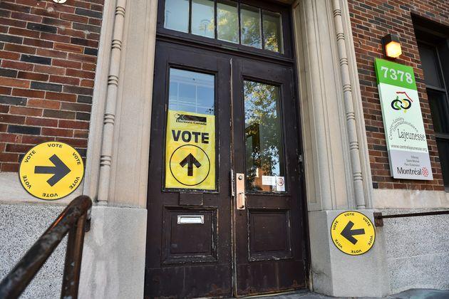 10月21日にモントリオールの投票所で選挙日にカナダの有権者に署名します。