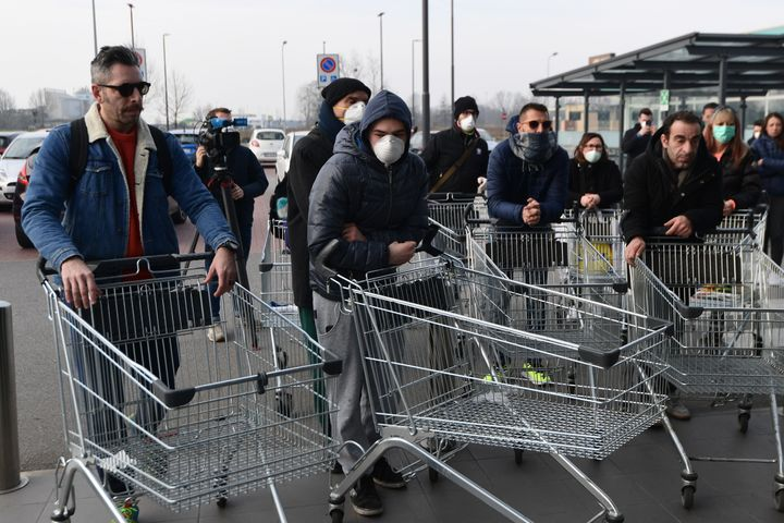 Residents wearing respiratory mask wait to be given access to shop in a supermarket in small groups of forty people in the small Italian town of Casalpusterlengo.