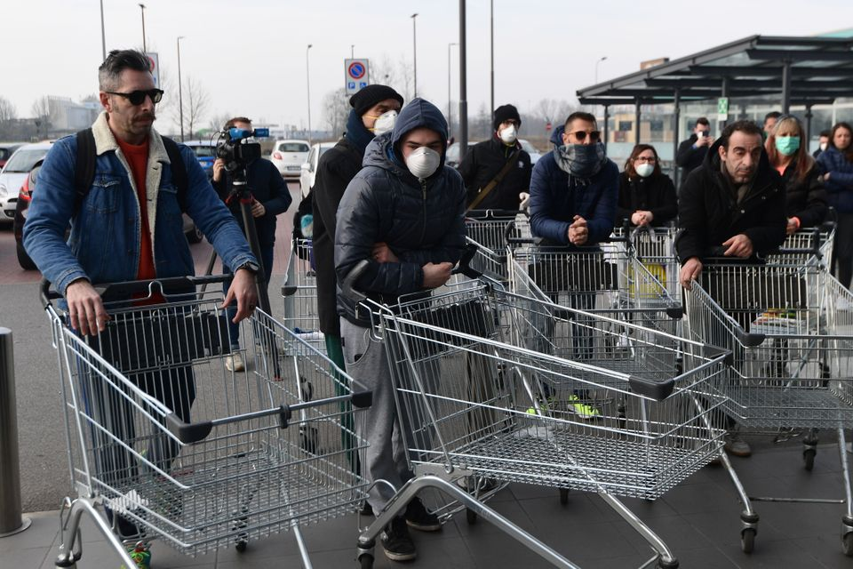 Residents wearing respiratory mask wait to be given access to shop in a supermarket in small groups of...