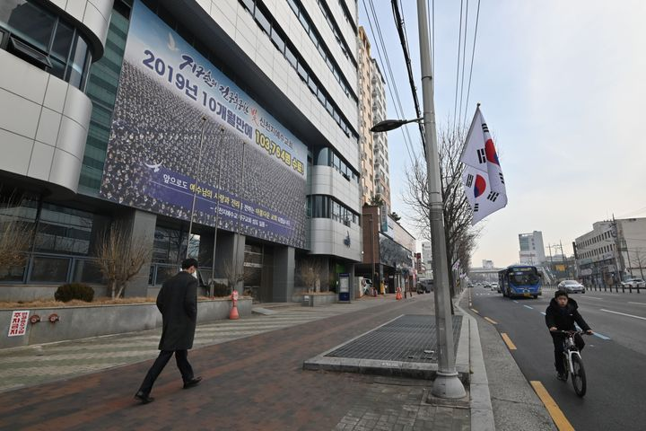 A man wearing a face mask walks in front of the Daegu branch of the Shincheonji Church of Jesus in the southeastern city of Daegu.
